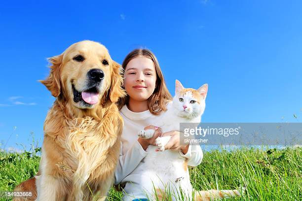 Girl, dog and a cat are enjoying outdoor.