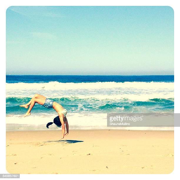 Girl doing a backflip on the beach
