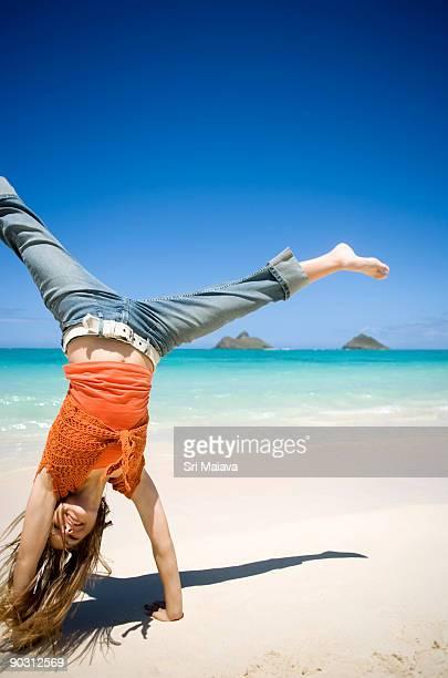 Girl doing a cartwheel at beach