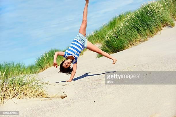 Girl Doing a Cartwheel at the Beach