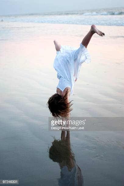 girl doing a cartwheel on the beach - girl in dress doing handstand stockfoto's en -beelden