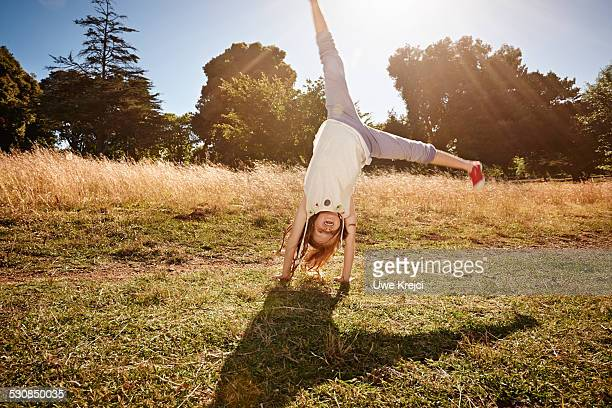 girl (8-10) doing a cartwheel - cartwheel stock pictures, royalty-free photos & images