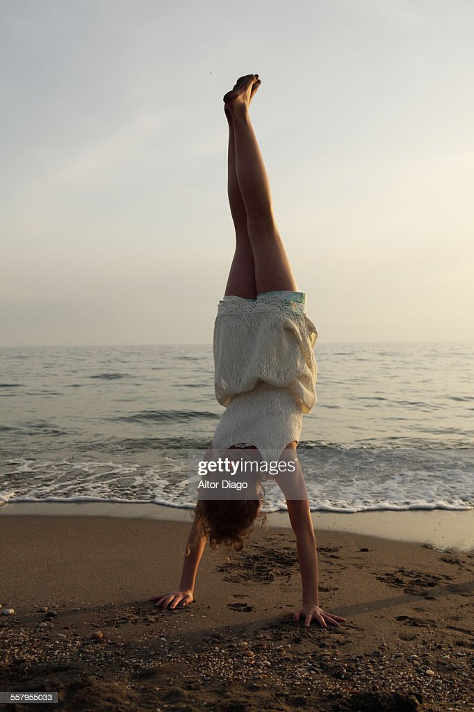 Girl doing a handstand at the beach : Stock Photo
