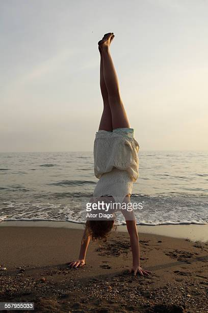 girl doing a handstand at the beach - girl in dress doing handstand stockfoto's en -beelden