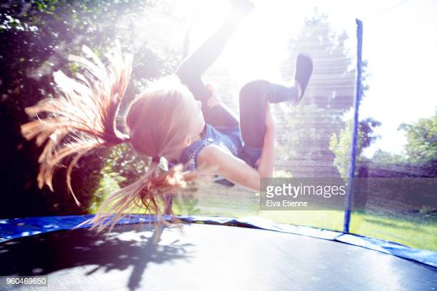 Girl (10-11) doing a somersault on a trampoline