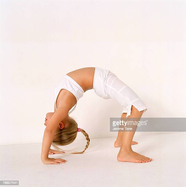 girl doing backbend - little girls bent over stock photos and pictures