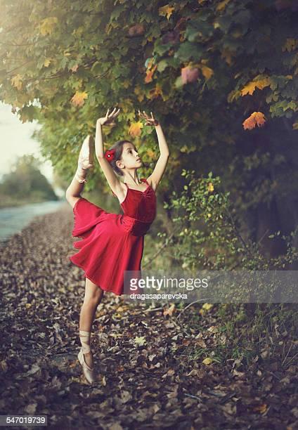 Girl doing ballet outdoors in red dress