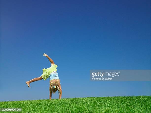 Girl (5-7) doing cartwheel in field
