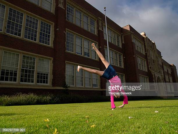 Girl (10-12) doing cartwheel in front of school