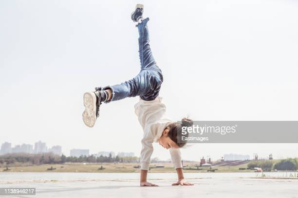 girl doing cartwheel in park - gymnastics stock pictures, royalty-free photos & images