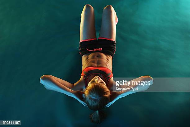 Girl doing crunches, green background
