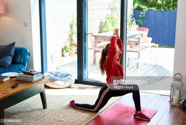girl doing fitness class on tv in living room - home workout stock pictures, royalty-free photos & images