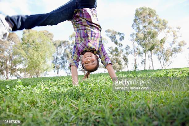 girl (10-12) doing hand stand in park - 12 13 jaar stockfoto's en -beelden