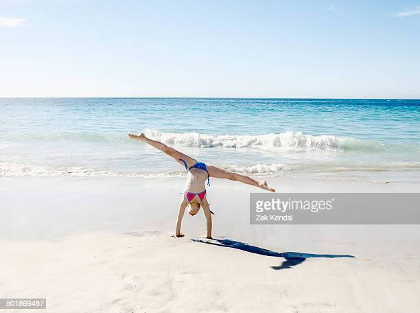 girl doing handstand and splits on beach - doing the splits stock photos and pictures
