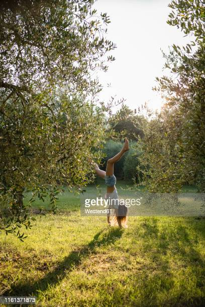 girl doing handstand on a meadow, tuscany, italy - europa meridionale foto e immagini stock