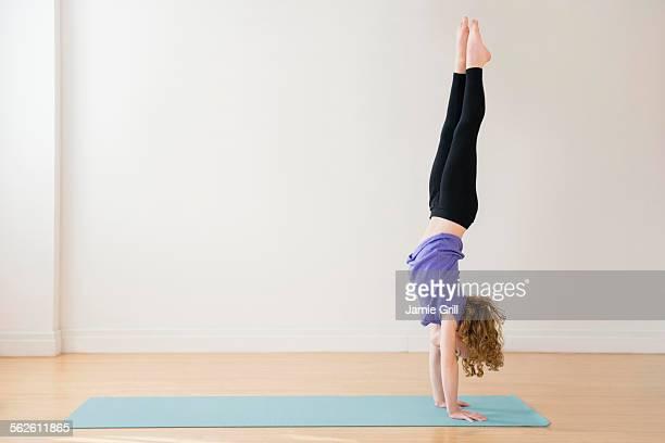 Girl (10-11) doing handstand