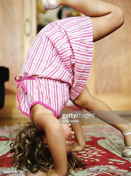 girl (5-7) doing handstand, side view - girl in dress doing handstand stock photos and pictures