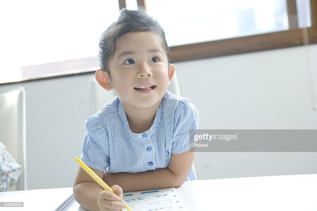 Girl doing her homework and looking away, smiling : Stock Photo