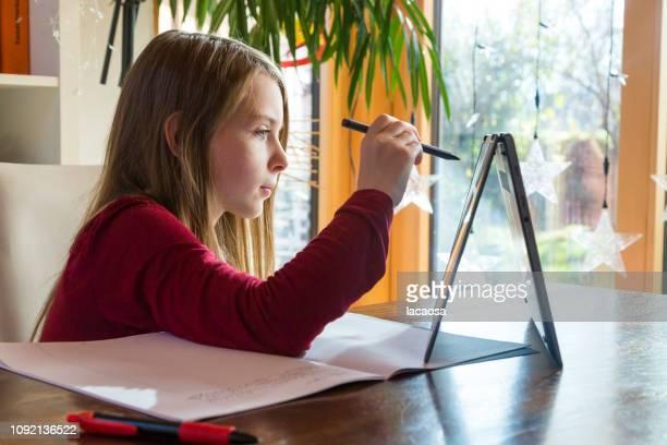 girl doing her homework using laptop