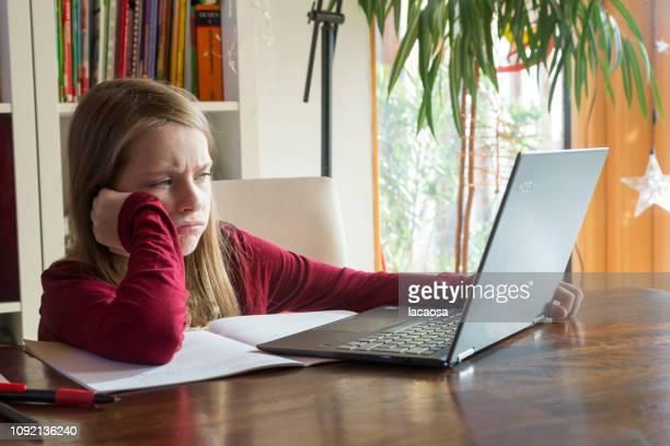 girl doing her homework with laptop
