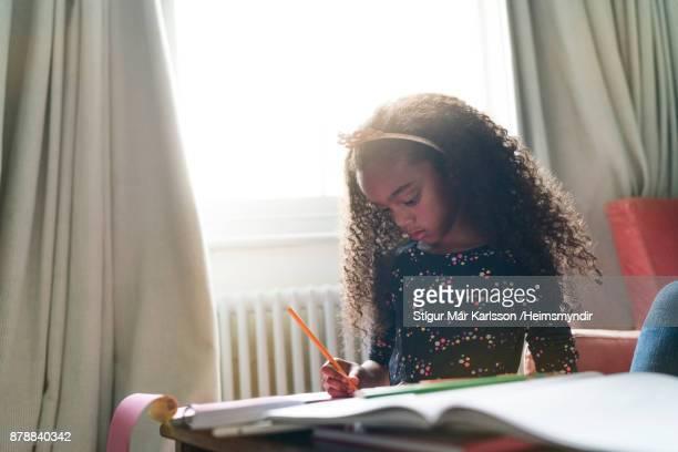 Girl doing homework against window in bedroom