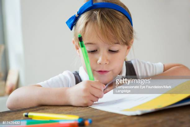 girl doing homework at kitchen table - hair bow stock pictures, royalty-free photos & images
