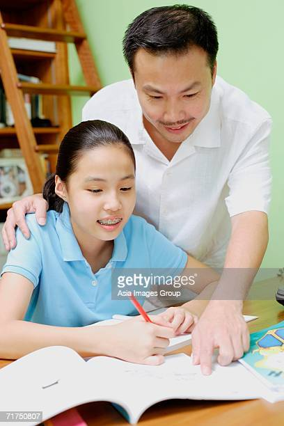 Girl doing homework, father standing next to her, pointing at book