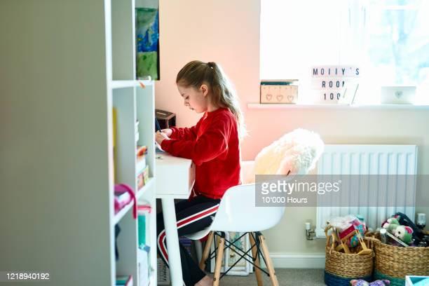 girl doing homework in bedroom during lockdown - inquadratura fissa foto e immagini stock