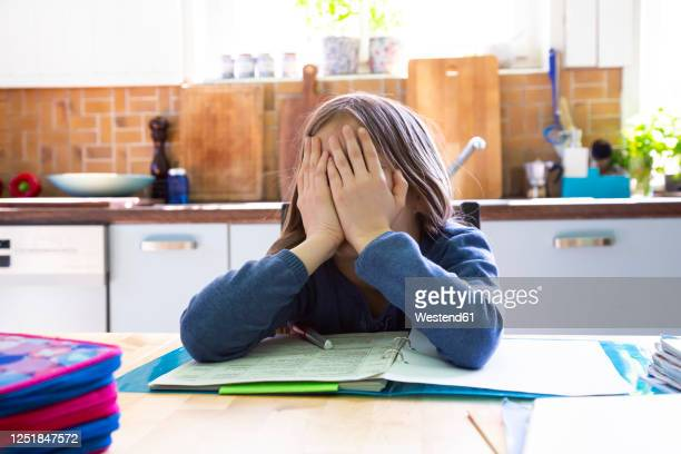 girl doing homework in kitchen at home, hands on face - sad child stock pictures, royalty-free photos & images