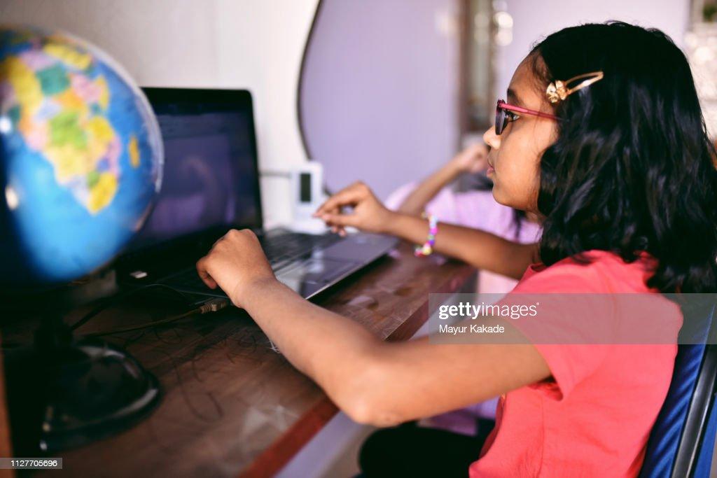 Girl doing homework on laptop : Stock Photo