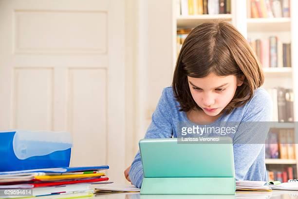 girl doing homework with tablet