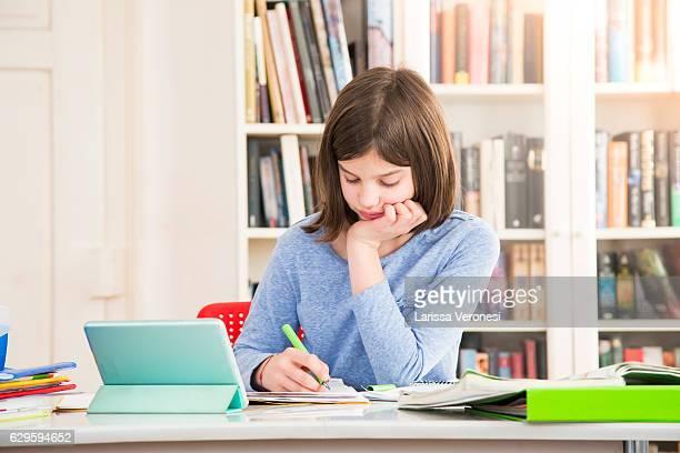 girl doing homework with tablet - hausaufgabe stock-fotos und bilder