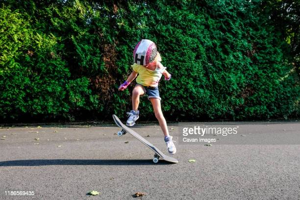 girl doing ollie trick on skateboard - ollie pictures stock pictures, royalty-free photos & images