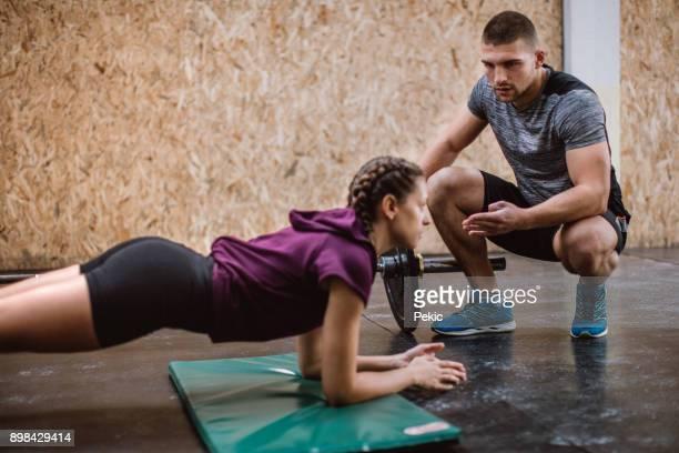 Fille de faire de l'exercice de la planche avec l'aide de l'instructeur de conditionnement physique