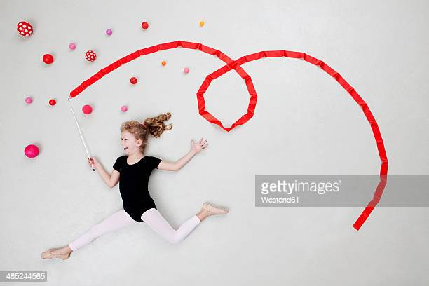 Girl doing rhythmic gymnastics with balls and ribbon