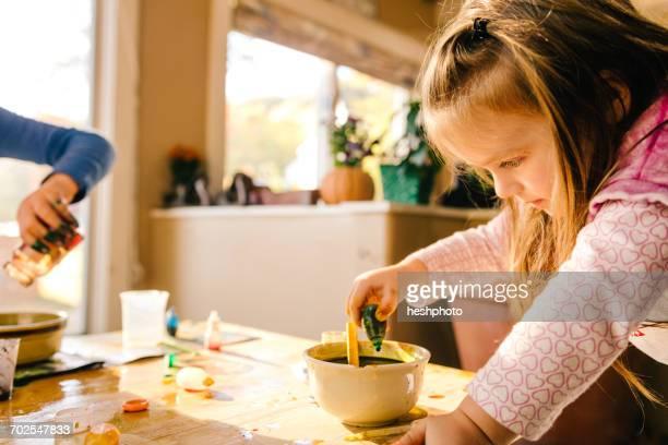 girl doing science experiment, dropping green liquid into bowl - heshphoto - fotografias e filmes do acervo