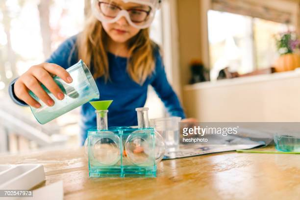 girl doing science experiment, pouring liquid into flask - heshphoto imagens e fotografias de stock