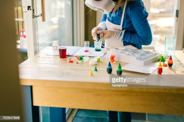 Girl doing science experiment, squeezing liquid into measuring cup