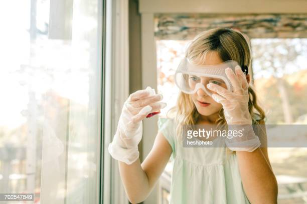 girl doing science experiment, staring at measuring flask - heshphoto imagens e fotografias de stock