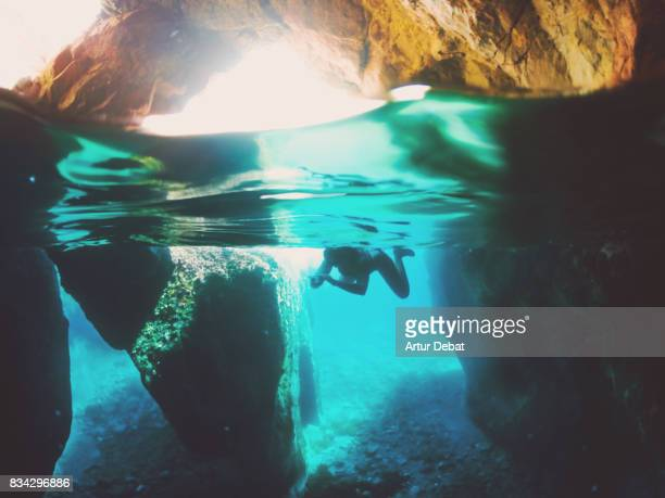 Girl doing snorkel exploring the natural cave in the shoreline of Costa Brava Mediterranean Sea during summer vacations in a paradise place taking picture with dome cover and underwater view.