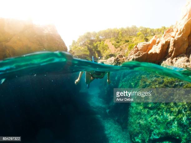 girl doing snorkel exploring the natural cave in the shoreline of costa brava mediterranean sea during summer vacations in a paradise place taking picture with dome cover and underwater view. - mittelmeer stock-fotos und bilder