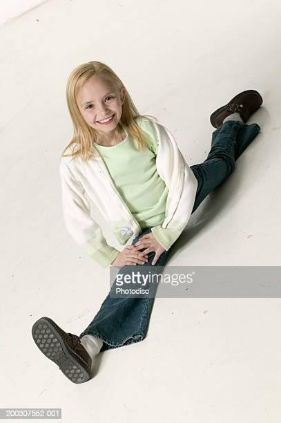 Girl (6-7) doing splits in studio, portrait, elevated view