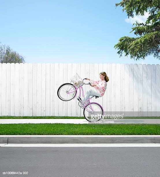 Girl (9-10) doing wheelie with stuffed animal in basket of bicycle