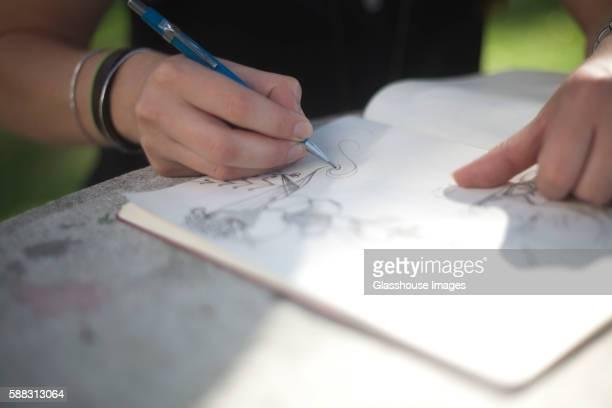 Girl Doodling in Sketchbook