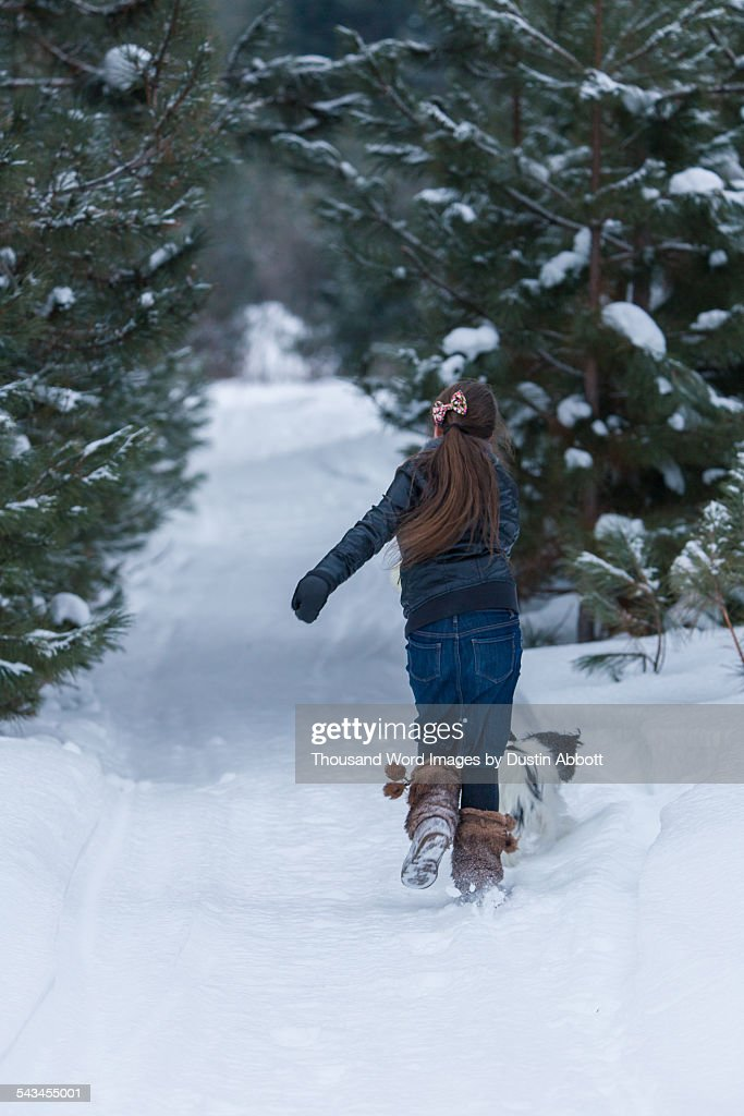 Girl Dragged by Dog in Snow : Stock Photo