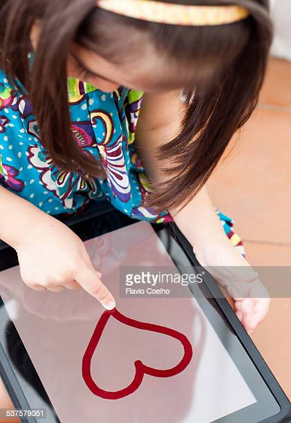 Girl drawing a heart with a digital tablet