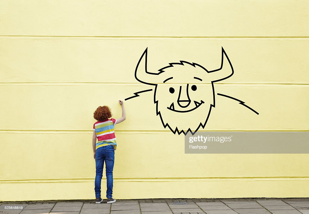 Girl drawing a picture of a monster on a wall : Stock Photo