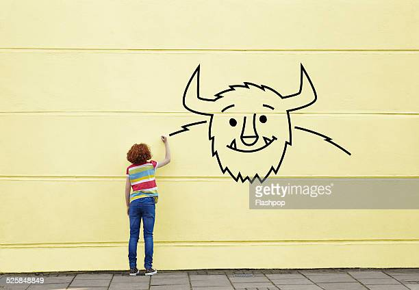 girl drawing a picture of a monster on a wall - image stockfoto's en -beelden