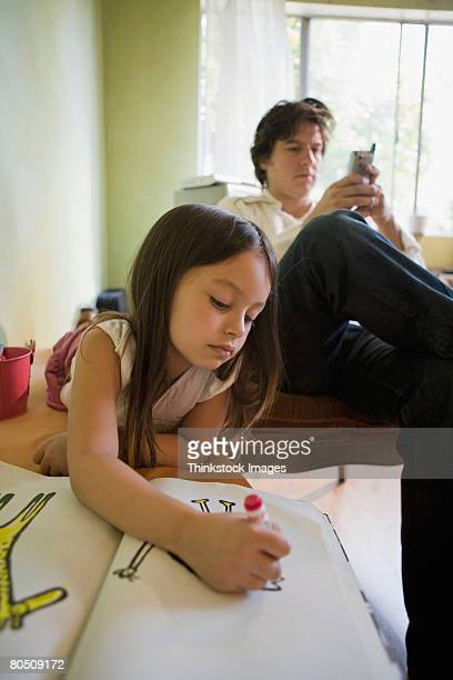 Girl drawing and man with cell phone