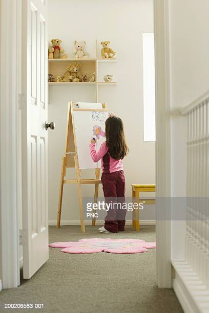 Girl (4-6) drawing at easel, rear view